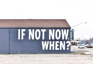 white concrete building with if not now, when? text