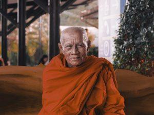 man wearing orange shirt sitting on bench