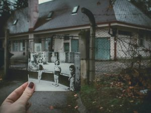 person holding photo of three girls near chainlink fence